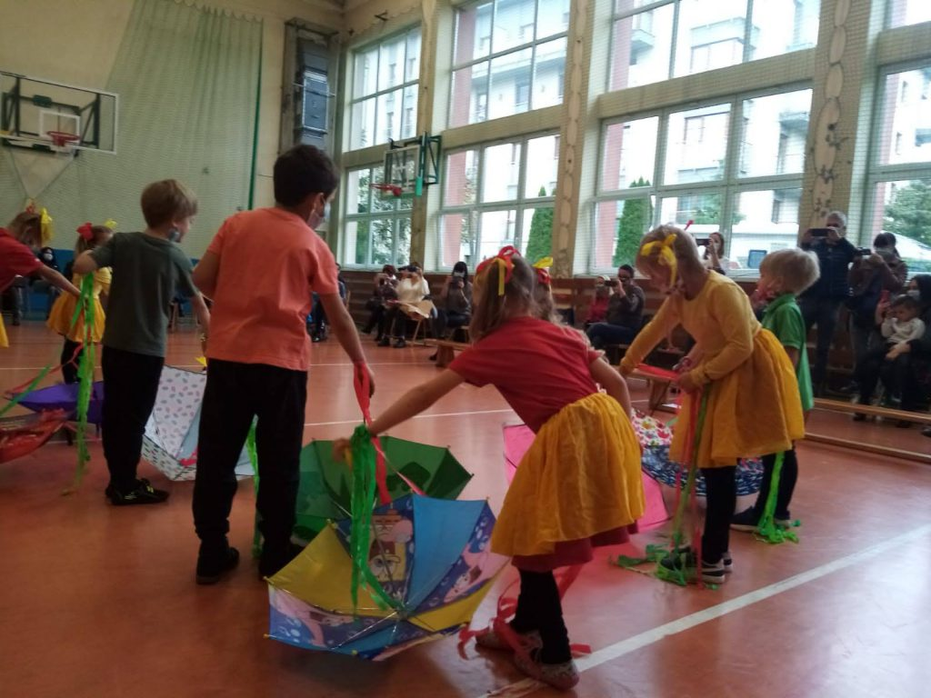 Przedszkolaki tańczące z parasolkami.