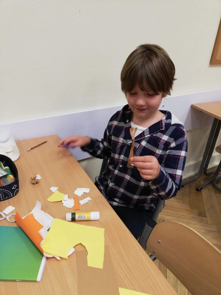 Uczniowie budujący elementy makiety - budynki i frzewa.