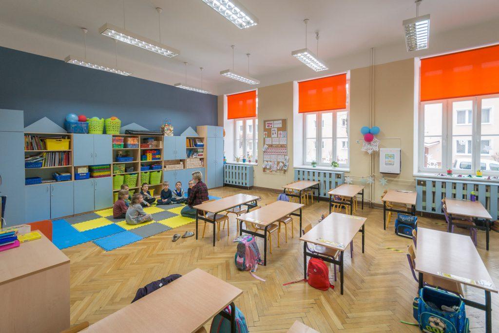 widok sali lekcyjnej, ławki, z tyłu sali siedzą na kolorowej macie dzieci z nauczycielem, za nimi niebieski regał z zabawkami, książkami.