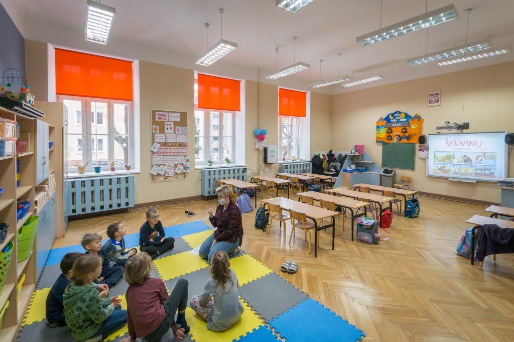 Widok sali, na pierwszym planie grupa dzieci z nauczycielem, siedzą na kolorowej macie. Po prawej stronie na ścianie znajduje się tablica multimedialna.